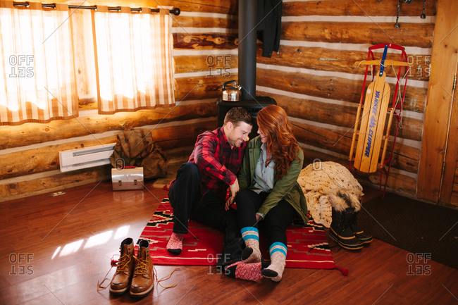 Couple laughing while sitting on floor at home