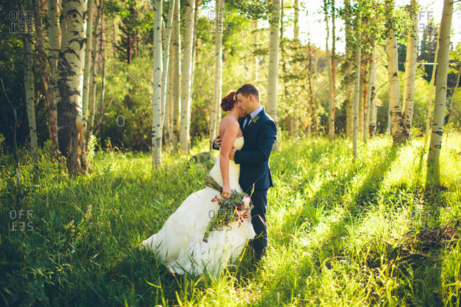 Newlyweds posing in forest