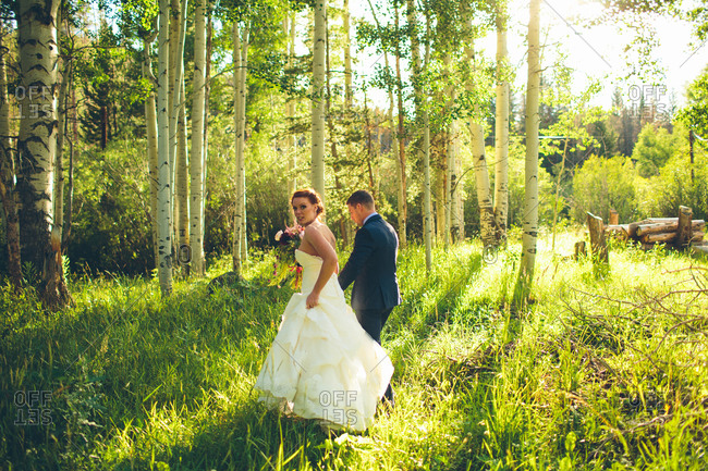 Newlyweds walking in forest