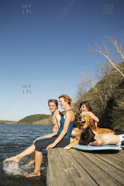 A family and their retriever dog on a jetty by a lake