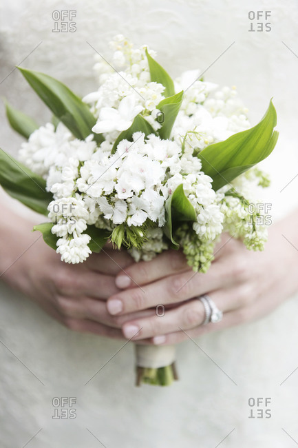 Mid section view of bride holding small bridal bouquet