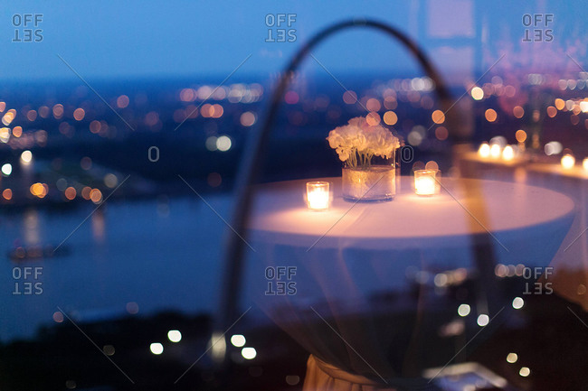 Round table with bouquet and candles reflecting in a window