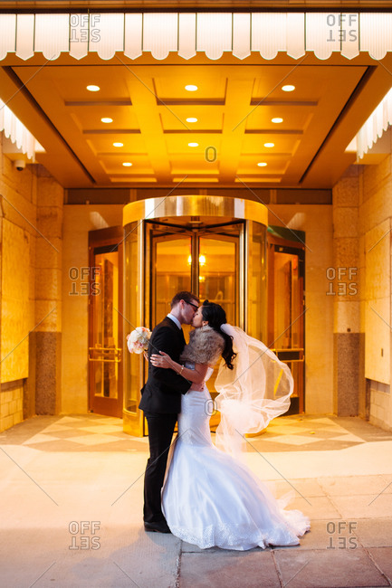 Wedding couple kissing  in hotel lobby