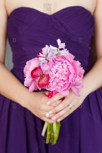 Mid section view of bridesmaid holding a bouquet