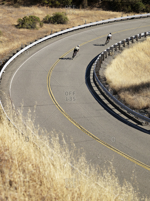 Two cyclists rounding a turn on a highway in Northern California