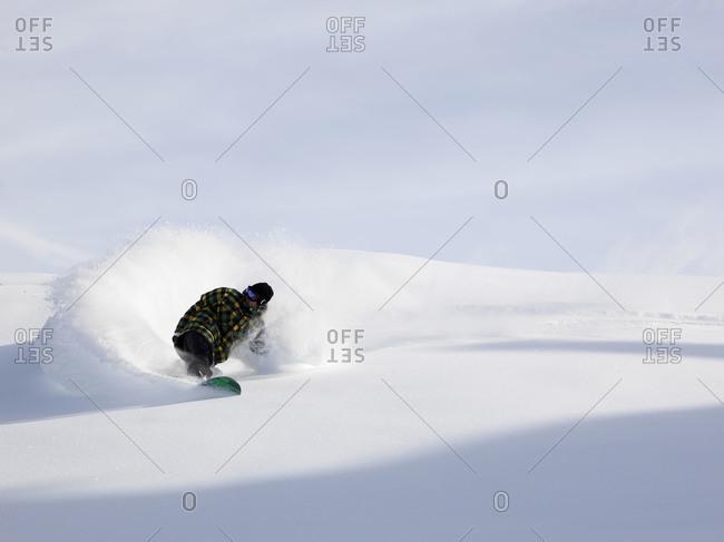 Snowboarder cutting through powdery snow