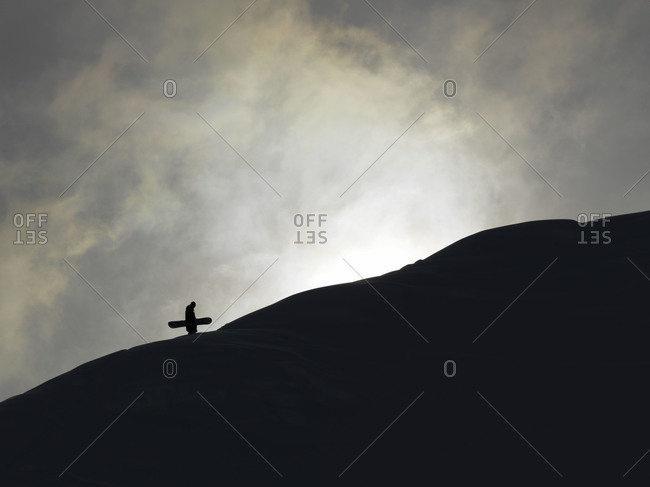 Silhouette of snowboarder climbing up a mountain