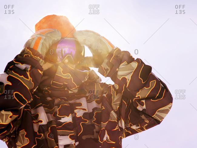 Snowboarder adjusting his goggles