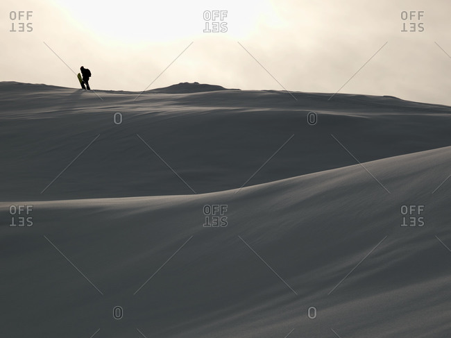 Silhouette of a snowboarder hiking up powdery landscape