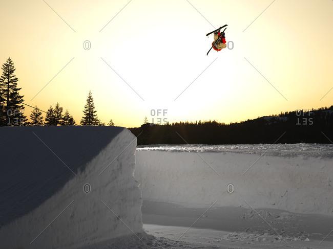Skier hitting a park jump at sunset