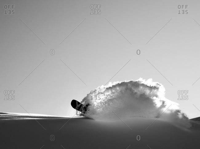Snowboarder carves a powdery turn
