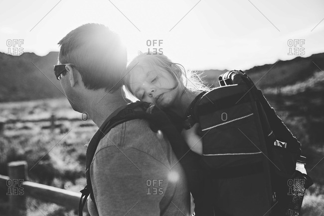 Father carrying his sleepy daughter in a back-pack as the sun goes down behind them