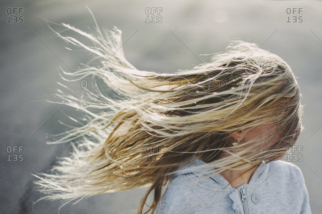 A blonde girl's hair blowing in the wind, obscuring her face