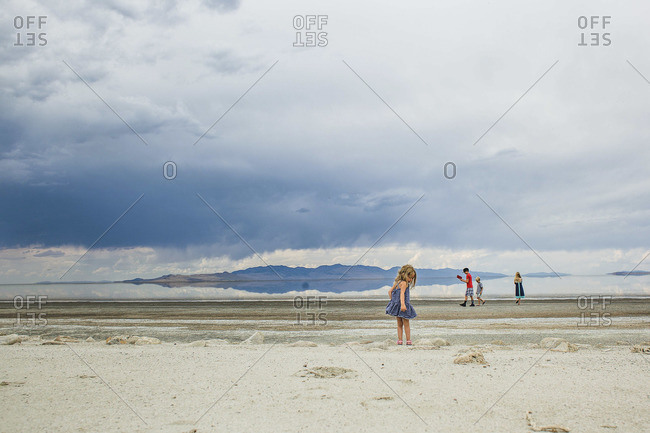 Children walk and play along a desolate shoreline