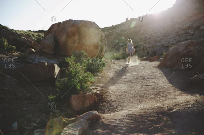 Girl walking by boulder in rocky wilderness