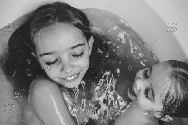 Black and white image of sisters sharing a bath