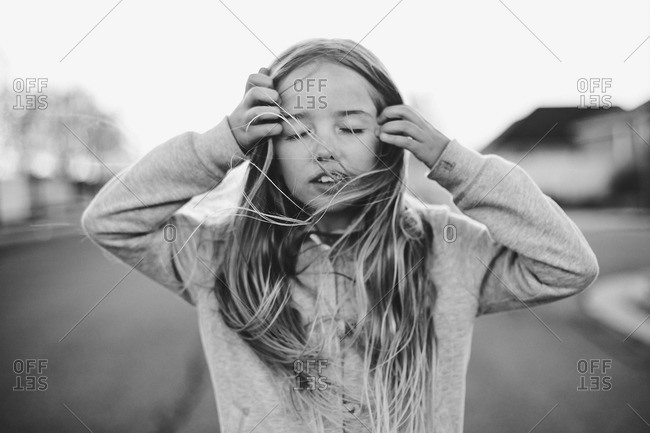 Black and white image of girl pulling hair from face