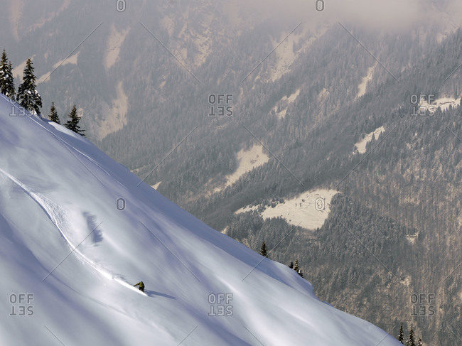 Snowboarder going down steep slope