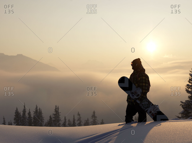 Snowboarder looking down a mountain top