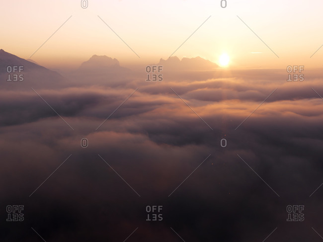 Winter sunrise over mountain top clouds