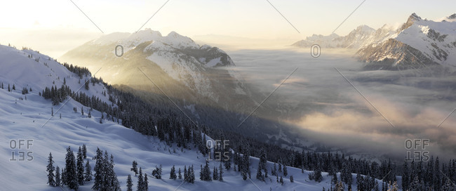 Foggy morning over snow covered mountains