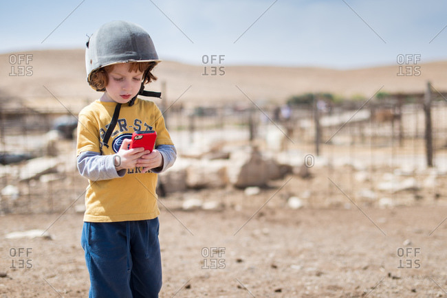 Redhead wearing helmet and using a smartphone