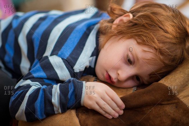 Boy resting on leather ottoman