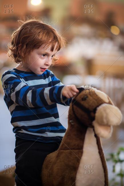 Redhead boy on toy horse