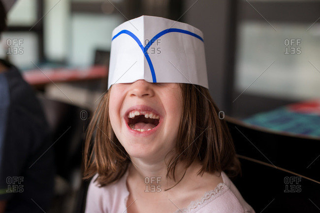 Girl hiding under paper hat