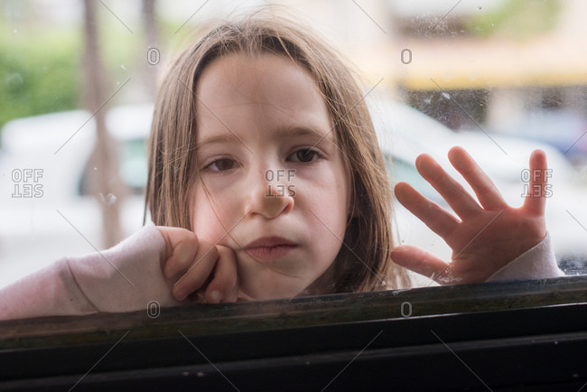 Little girl pushing her face against a window