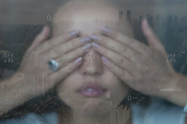 A woman covers her eyes