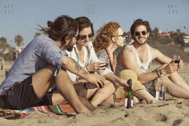 Friends drinking wine at a beach