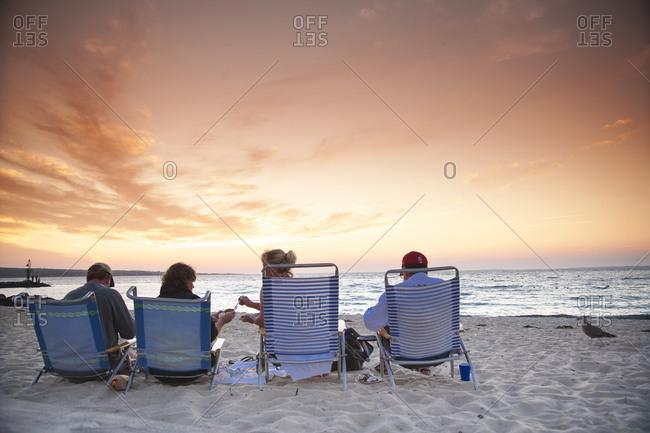 Friend enjoying a beach picnic and sunset