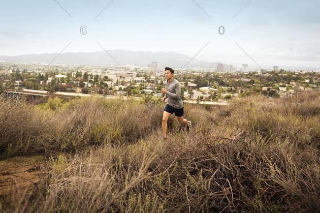 Young man jogging through scrubland above a small city