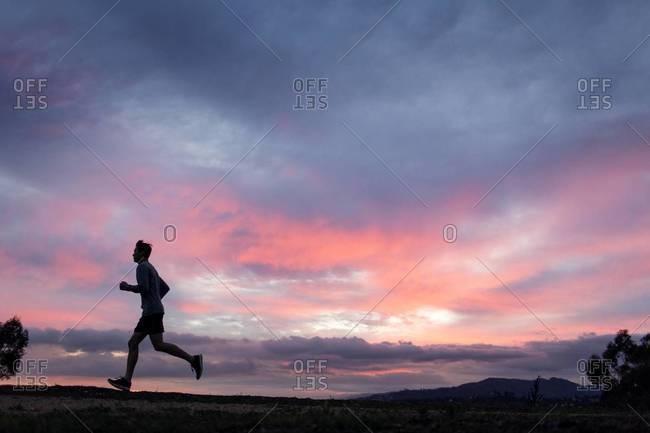A young man runs along a ridge under a colorful sunset sky