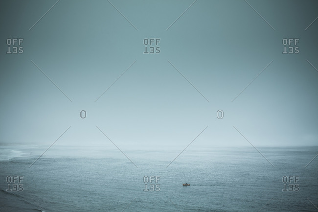 A small motorboat approaches the coast of Oregon on a foggy day