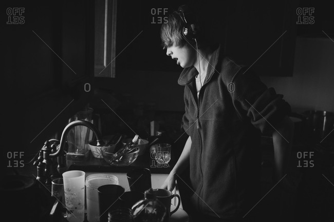 Boy listening to music while washing dishes