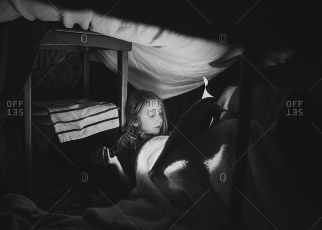 Girl reading in a blanket fort