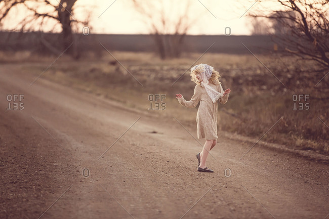 Girl dancing on a gravel road