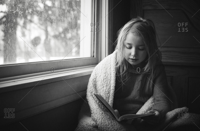 Girl reading a book by a window
