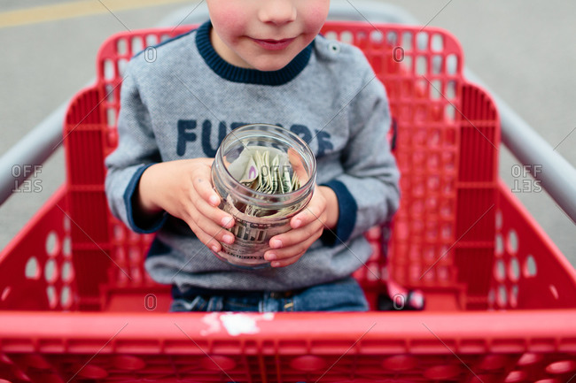 Boy sitting in a shopping cart with a money jar in his hands