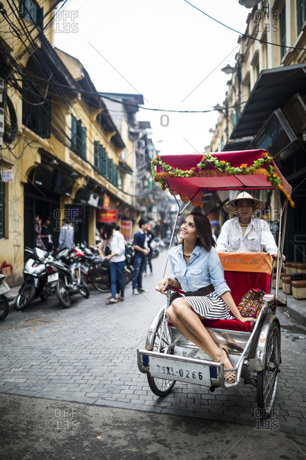 Old Quarter, Hanoi, Vietnam - April 3, 2014: A young woman rides a cyclo through the streets of the Old Quarter in Hanoi, Vietnam.