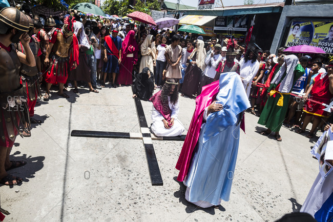 Pampanga, Philippines - April 18, 2014: Ruben Enaje, playing the role of Jesus Christ, is led through the streets of Cutud, the Philippines, during the Holy Week festival.