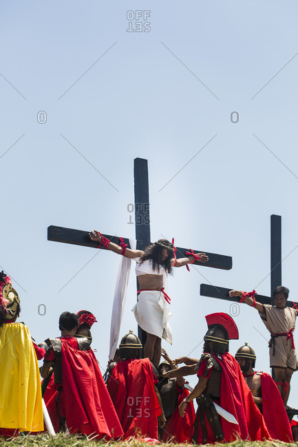 Pampanga, Philippines - April 18, 2014: Ruben Enaje, playing the role of Jesus Christ, is crucified on a cross, with nails in his hands and feet, in Cutud, the Philippines, during the Holy Week festival.