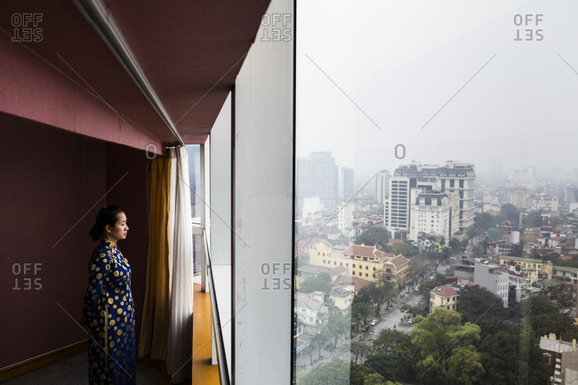 Hanoi, Vietnam - March 15, 2014: An employee wearing an ao dai looks out of the window of the Melia hotel at downtown Hanoi, Vietnam.