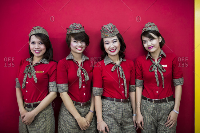 Ho Chi Minh City, Vietnam - February 24, 2014: Female flight hostesses pose for a photograph at the Vietjet Air offices in Ho Chi Minh City, Vietnam. The airline seemingly employs gangs of young, attractive female air hostesses to lure customers.