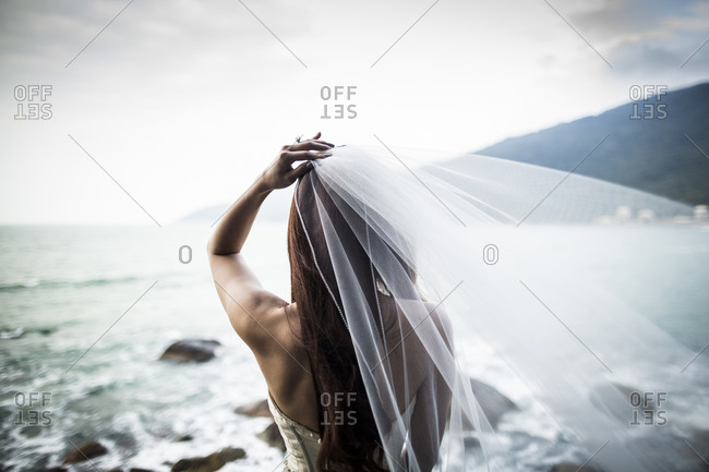 A young bride holds her veil as she looks over the ocean in central Vietnam.