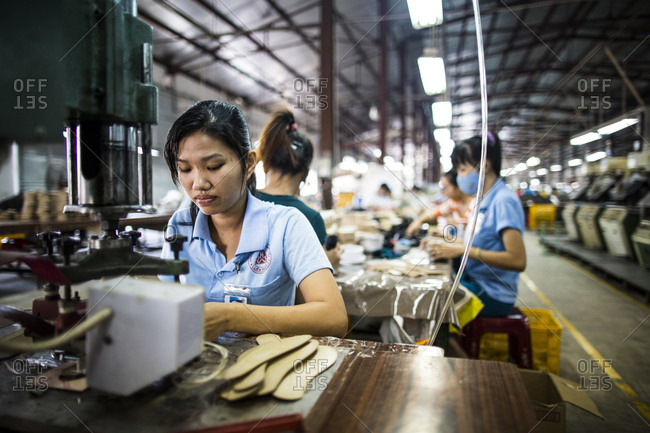 Binh Duong, Vietnam - December 9, 2013: A young female factory worker assembles shoes at the Lien Phat factory in Binh Duong province, Vietnam.