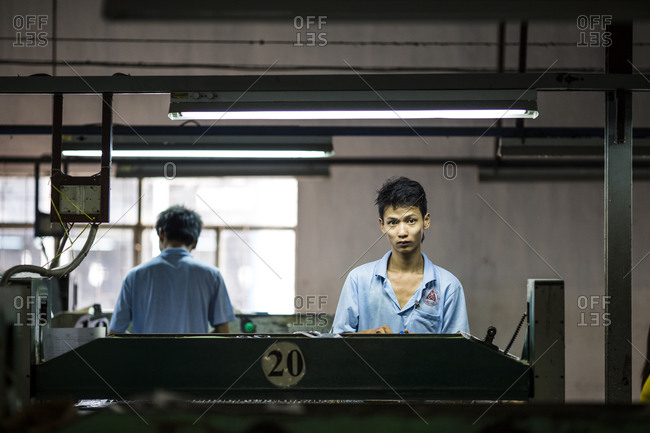 Binh Duong, Vietnam - December 9, 2013: A factory worker assembles shoes at the Lien Phat factory in Binh Duong province, Vietnam.