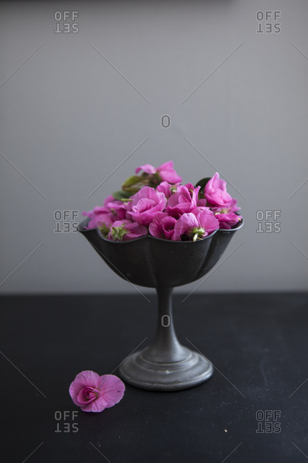 Pink flowers in a pewter stand.